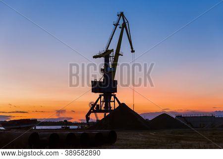 Port crane on sunset - industry background
