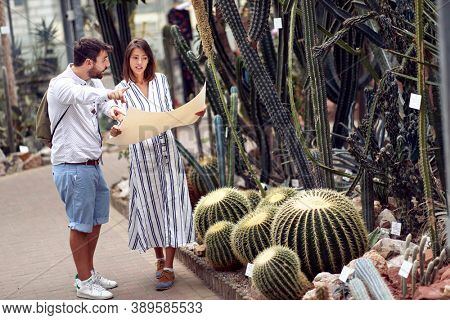 Male visitor and female guide searching botanical garden map at the conservatory