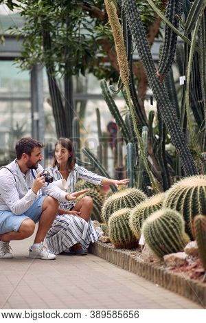 Male visitor and female guide talking about beautiful cactuses at the conservatory