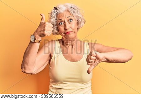 Senior grey-haired woman wearing casual clothes doing thumbs up and down, disagreement and agreement expression. crazy conflict