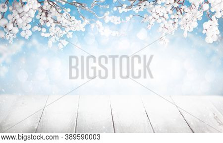 Christmas or Winter scene with snowy branches over snowy white wooden table. Winter background with copy space