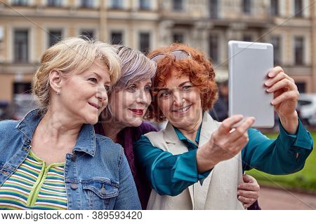 Three Smiling Older Caucasian Women Make Selfie In The Center Of A European City With A Tablet Compu