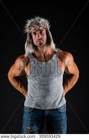 Strong And Fit. Bodybuilder Wear Fur Hat In Casual Style Black Background. Bodybuilder Show Biceps T