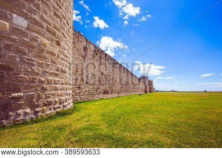 Southern France. Around the walls are green lawns. Picturesque powerful gates and fortifications defend the port city of Aigues-Mortes. Journey to History