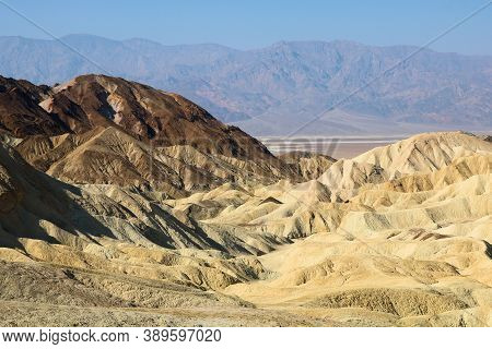 Rural Canyon Surrounded By Arid Hills With A Plateau And Barren Mountains Beyond Taken At Zabriskie