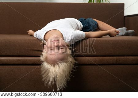 Blond Boy Lies On Couch With His Head Hanging. Child Is Tired. Wrong Sleeping Position Of Child.