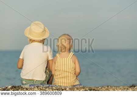 Back View Brother And Sister Are Sitting On Beach And Looking At Sea. Carefree Childhood. Retro Phot