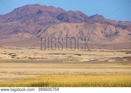 Arid Plateau With Sand Dunes And Barren Mountains Beyond Taken In The Rural Mojave Desert, Ca