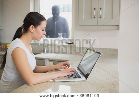Woman using a laptop in the kitchen with burglar standing at the window