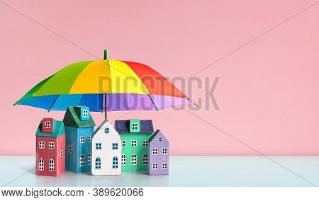 Houses Covered By Rainbow-colored Umbrella. Protection, Insurance Security Of Real Estate, Property
