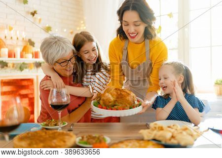 Happy Thanksgiving Day! Autumn feast. Family sitting at the table and celebrating holiday. Traditional dinner. Grandmother, mother and daughters.