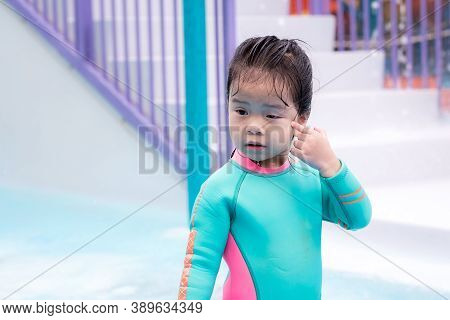Child Girl Wearing Swimsuit Is Scratching The Tail Of Eyes From Itching Or Debris In Her Eyes Or Fro