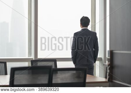 Rear View Of An Asian Business Man Standing In Front Of Office Window Thinking Hands In Pockets