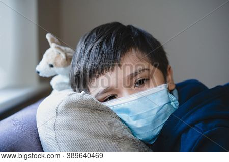 Sick Child Wearing A Protective Mask, Ill Kid In A Medical Face Mask Lying Head On Sofa With Sad Fac