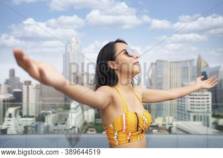 Asian Woman In Yellow Swimsuit Relax In Rooftop Swimming Pool With Bangkok City Background, This Ima
