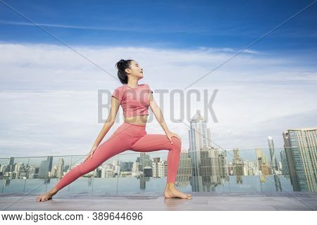 Asian Beautiful Woman In Pink Sports Uniform Doing A Yoga Exercise On Hotel Rooftop With Bangkok Cit