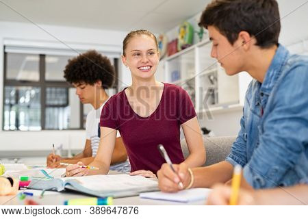 Young friends studying together in college classroom. Happy high school girl studying with guy during lesson. Two university students working together sitting at table doing assignments in library.