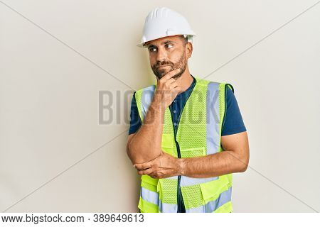 Handsome man with beard wearing safety helmet and reflective jacket thinking concentrated about doubt with finger on chin and looking up wondering