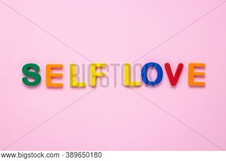 Self Love Text On Pink Paper Background Made From Colorful Plastic Letters. Multicolored Inscription