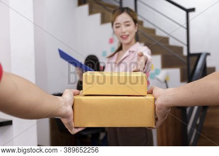 Hand Of Delivery Man Delivering Package To Homeowner. Woman Accepting A Delivery Of Boxes From Deliv