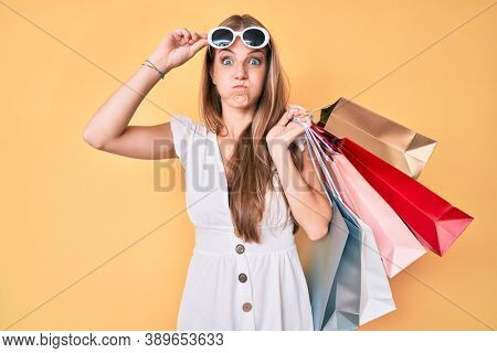 Young blonde girl holding shopping bags puffing cheeks with funny face. mouth inflated with air, catching air.