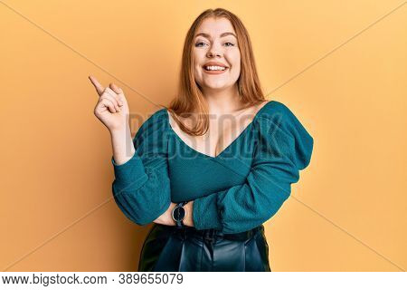 Young beautiful redhead woman wearing elegant and sexy look with a big smile on face, pointing with hand and finger to the side looking at the camera.