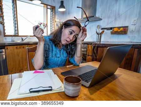 Attractive Young Business Woman Working From Home On Her Computer Stressed, Tired And Overwhelmed