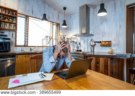 Attractive Young Business Man On Computer Working From Home Feeling Stressed, Tired And Overwhelmed