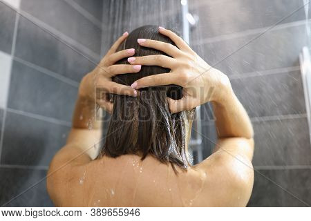 Woman Stands Under Shower And Washes Her Hair. Evening Showering And Fatigue Relief Concept