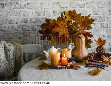 Lit Candles, Dry Maple Leaves, Pumpkin, Stack Of Books - Autumn Still Life Interior Decoration House