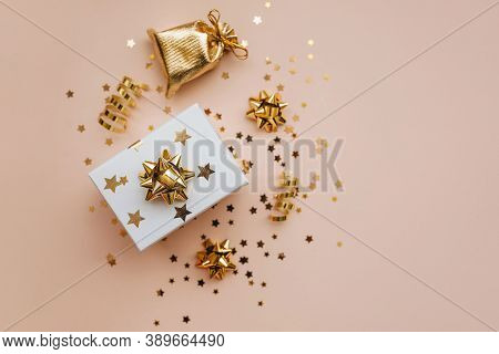 Gift Box And Various Golden Items On A Pink Background. Festive Conceptual Christmas Or New Year Bac