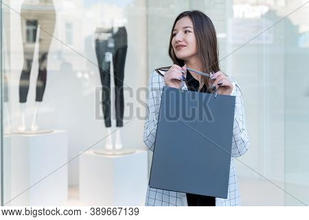 Happy Young Woman With Paper Black Shopping Bag In Hand. Showcase On Background. Space For Text. Bla