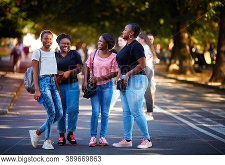 Beautiful African American Women, Laughing Friends Having Fun While Walking On The Street