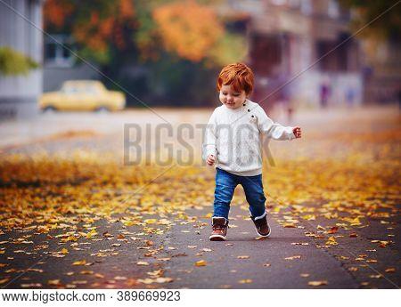 Cute Redhead Baby Boy Running The Autumn Street Among Fallen Leaves
