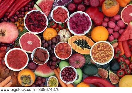 Immune boosting healthy food for good health high in lycopene, anthocyanins, antioxidants, vitamins, minerals & dietary fibre. With fruit & vegetables, loose & in round bowls. Plant based vegan foods.
