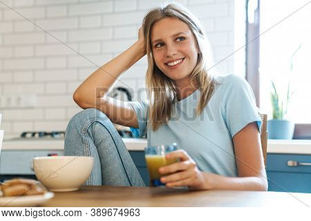 Beautiful joyful girl smiling and drinking juice while having breakfast at home kitchen