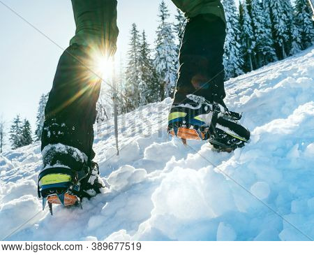 Close Up Shot Of Mountain Boots With Crampons And Snow Gaiters With Backlight Sun Beams And Snowy Sp
