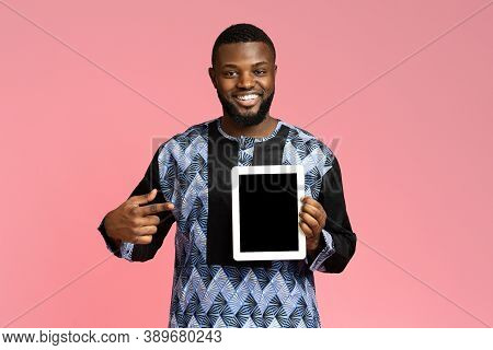 Smiling Black Guy Pointing At Digital Tablet With Empty Screen, Wearing Traditional African Costume.