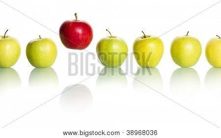 Single red apple floating above a row of green apples isolated on white background. poster