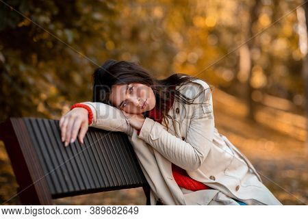 Unhappy Young Woman In Casual Clothes Sitting On Bench At Autumn Park. Caucasian Millennial Lady Suf