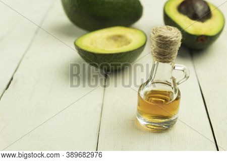 Avocado Oil And Fresh Avocado On The Table. Avocado Oil In A Glass Bottle. Avocado Cut In Two