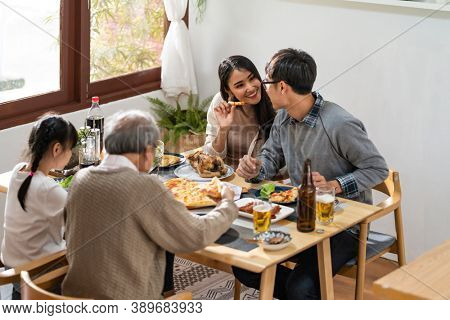 Happy asian multigenerational family of dad mom daughter girl and grandfather eating lunch together at home.  Happy family engagement togetherness concept.