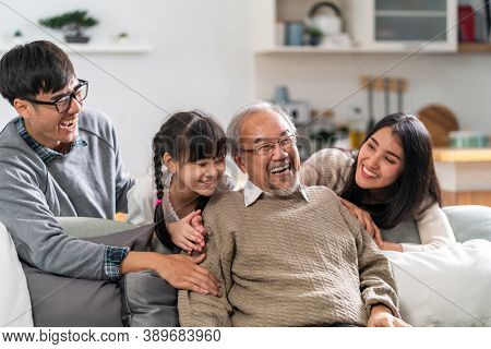 Group Portrait of Happy multigenerational asian family sit on sofa couch in living room with smile. Muti genration family happiness concept.