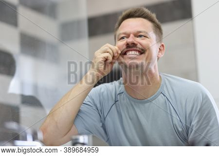 Man Smiles And Holds His Mustache In Front Of Mirror. How To Shave Your Mustache Concept