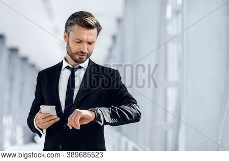 Just In Time. Handsome Bearded Businessman Checking Time On His Watch, Using Mobile Phone While Wait