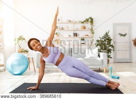 Millennial Black Woman Doing Side Plank On Yoga Mat Indoors. Full Length Portrait Of Fit African Ame