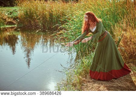 Historical reconstruction of ancient Celtic times. Beautiful red haired girl in a traditional green celtic dress stands by the lake.