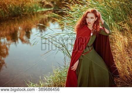 Beautiful red haired girl in a traditional green celtic dress and a red cloak stands by the lake. Historical reconstruction of ancient Celtic times.