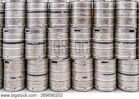 Wall Of Used And Scratched Stainless Steel Beer Barrels Or Kegs. Stacked In A Row Large Silver Or Me