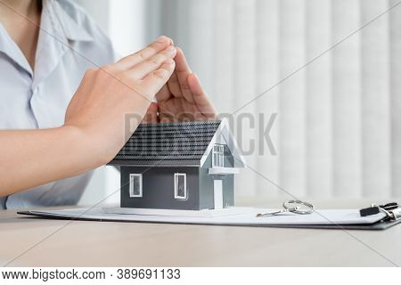 The Hand Of A Real Estate Investment Agent Who Protects The Home Design With Lease Documents, Contra